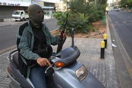 A Sunni gunman holds his AK-47 as he rides a scooter on a blocked street leading to a Shiite neighborhood after overnight clashes between Sunni and Shiite gunmen in Beirut, Lebanon.