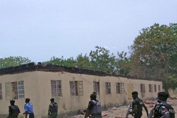 FILE - In this file photo taken on Monday, April, 21. 2014, security walk past a burnt out government secondary school in Chibok, where gunmen abducted more than 200 students, Chibok, Nigeria. (AP Photo/ Haruna Umar,File)