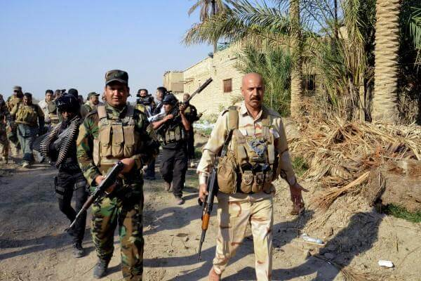 Iraqi security forces and Shiite militiamen patrol Jurf al-Sakhar,  south of Baghdad, Iraq, on Oct. 25, 2014. (AP Photo)