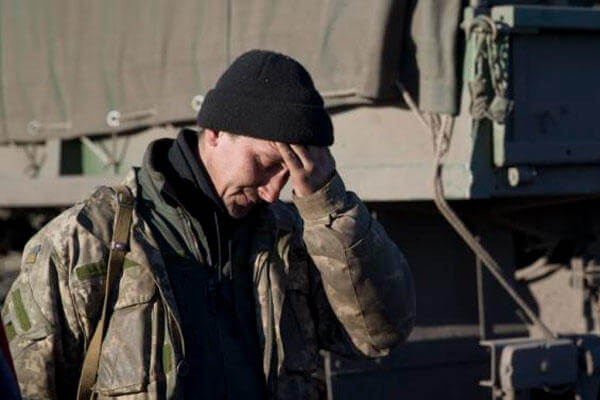 A Ukrainian serviceman touches his forehead outside Artemivsk, Ukraine, while pulling out of Debaltseve, Wednesday, Feb. 18, 2015. (AP Photo/Vadim Ghirda)
