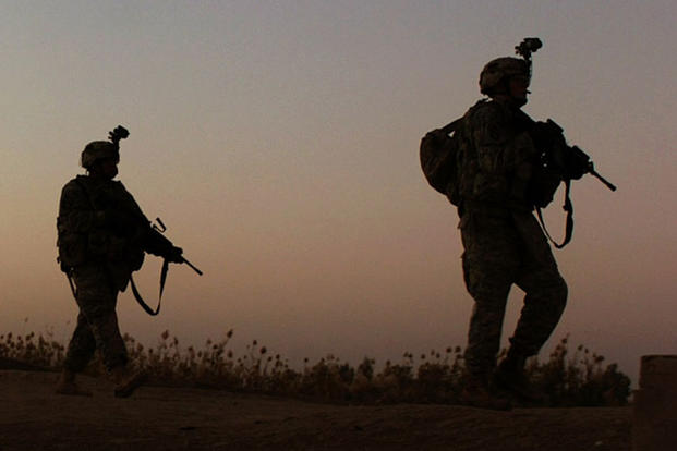 In a 2007 file photo, soldiers with 2nd Brigade Combat Team, 101st Airborne Division (Air Assault), move toward an objective while searching for detonation cord after an IED detonated in Iskandariyah, Iraq. Army photo