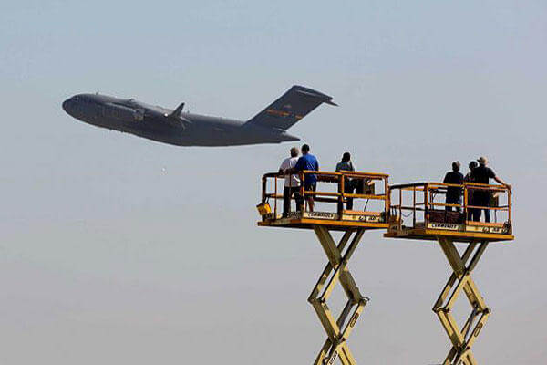 Boeing workers stand on platforms as they wave at their last C-17 Globemaster III cargo jet built for the U.S. Air Force as it flies away at the aerospace company's plant in Long Beach, Calif., on Sept. 12, 2013.