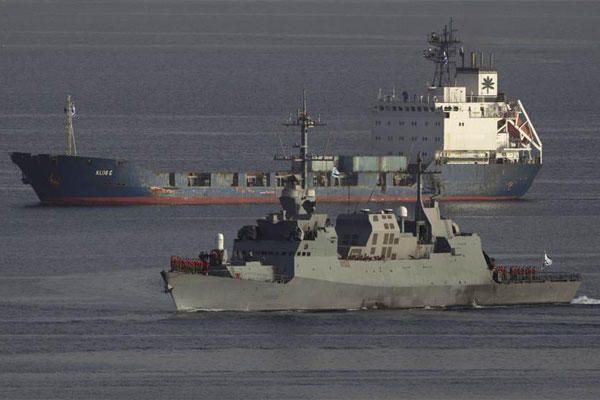 An Israeli naval warship escorts the seized Klos-C cargo ship as it enters the port at the Red Sea resort city of Eilat, southern Israel, Saturday, March 8, 2014. (AP Photo/Ariel Schalit)
