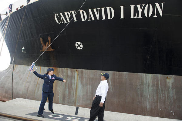 Capt. Dana M. Lyon, widow of Capt. David I. Lyon, prepares to break a champagne bottle on the hull of the Motor Vessel Capt. David I. Lyon during a christening and ship visit, Aug. 11, 2014. (U.S. Air Force photo/Tech. Sgt. Jason Robertson)