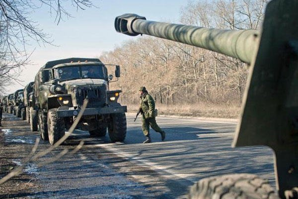 A Russia-backed separatist fighter walks by a convoy transporting artillery pieces , outside the city of Donetsk, Ukraine,Tuesday, Feb. 24, 2015. (AP Photo/Vadim Ghirda)