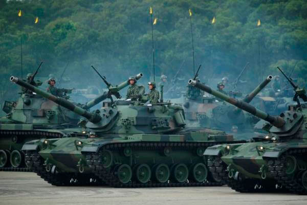 Taiwan's military maneuver battle tanks in front of thousands of spectators in a parade marking the 70th anniversary of the end of WWII, at the military base in Hsinchu, northern Taiwan, Saturday, July 4, 2015. AP