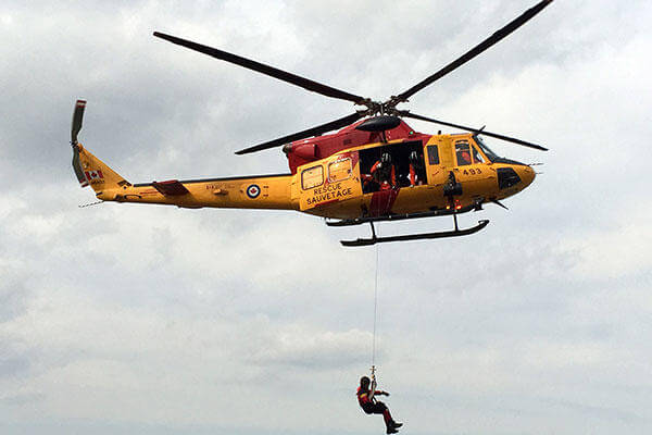 A Royal Canadian Air Force CH-146 Griffon helicopter conducts hoist evolutions during joint training operations with the U.S. Coast Guard in Barrie, Ontario, May 5, 2015. (U.S. Coast Guard photo)