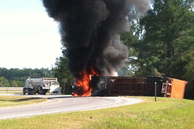 A semi-truck is engulfed in flames after an accident between the semi and a disabled vehicle caused it to flip. (U.S. Coast Guard photo courtesy of Coast Guard Sector Mobile)
