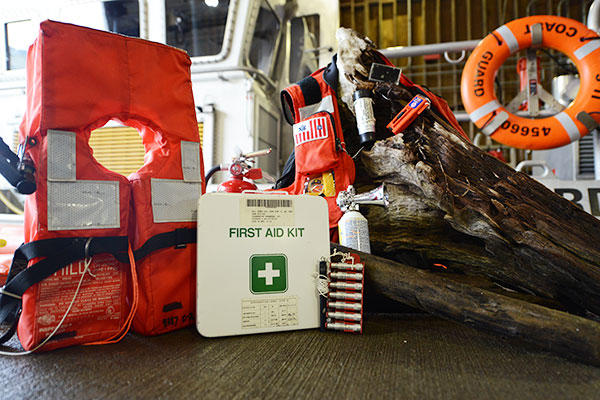 Key pieces of boating safety equipment, including a lifejacket, a first aid kit, a fire extinguisher, and visual distress signals. The Coast Guard urges boaters to carry survival gear like this. (U.S. Coast Guard/Seaman Sarah Wilson)