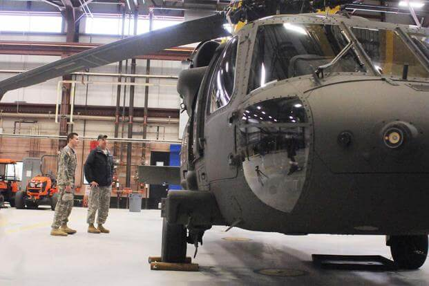 Jeff Gregg, UH-60M instructor with Science and Engineering Services, Inc., and Capt. Kristian Mroczko look at the outside of a new UH-60M Black Hawk.  (Photo by Michelle Kennedy)