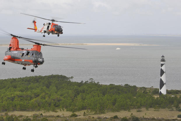 An MH-60 Jayhawk helicopter crew from Air Station Elizabeth City flies above a Marine Corps HH-46E Sea Knight helicopter crew from Air Station Cherry Point, Sept. 22, 2015, near Cape Lookout. (U.S. Coast Guard/Petty Officer 2nd Class Nate Littlejohn)