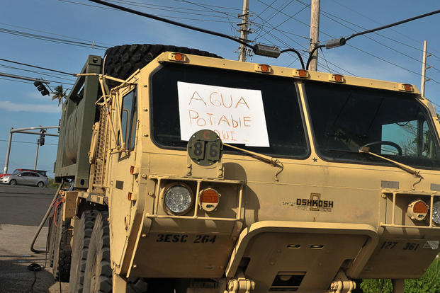 "A M977 Heavy Expanded Mobility Tactical Truck with 2,000 gallons of purified water from the Rosy Roads water station in Puerto Rico displays an ""Agua Potable Aqui"" (Potable Water Here) sign in the window, Oct. 14, 2017. (U.S. Army/Sgt. Michael Eaddy)"