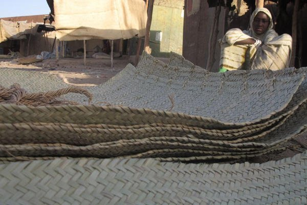 In this Wednesday, Feb. 20, 2013 photo, a young vendor waits for clients alongside woven reed mats of the type purchased by fleeing Islamists, apparently to camouflage their vehicles, in Timbuktu, Mali.AP Photo/Rukmini Callimachi