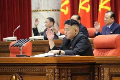 North Korean leader Kim Jong Un raises his hand with other officials during a recent meeting of the central committee in Pyongyang. He has vowed to restart a nuclear reactor that his father had agreed to shut down more than five years ago. Photo AP/KCNA