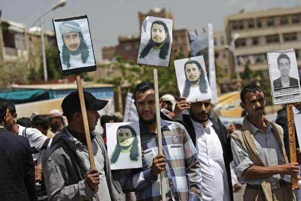 Yemeni protestors hold photos of their relatives detained in Guantanamo Bay prison during a demonstration in front of the U.S. embassy demanding their release, in Sanaa, Yemen, Monday, April 1, 2013. AP Photo/Hani Mohammed