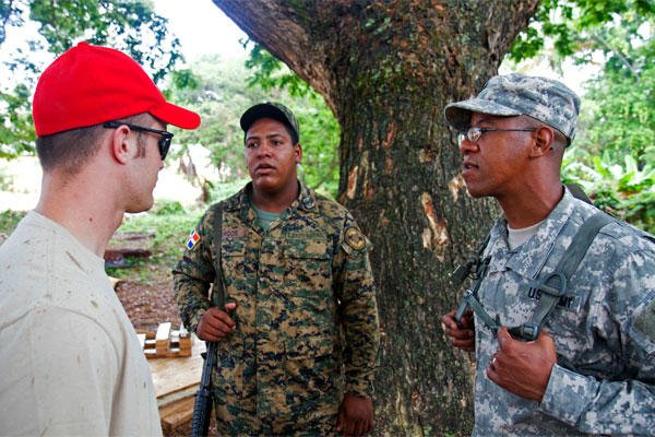 Army Sgt. Richard Mercedes interprets a conversation between Air Force Senior Airman Michael Hyer of the Ohio Air National Guard's 200th Red Horse Civil Engineering Squadron and Cpl. Ramon Burgos of the Dominican Republic's army.