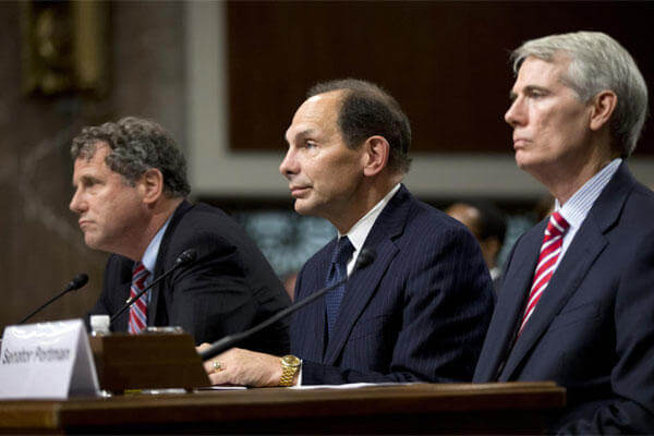 Veterans Affairs Secretary nominee Robert McDonald of Ohio flanked by Sens. Sherrod Brown, D-Ohio, left, and Rob Portman, R-Ohio, right, listen during a Senate Veterans' Affairs Committee hearings. (AP Photo)
