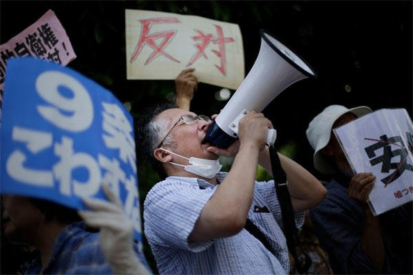 A man shouts slogans over a public-address system during a protest outside the Japanese prime minister's office in anticipation his government will reinterpret the constitution to allow Japan's military a larger international role in Tokyo. (AP photo)