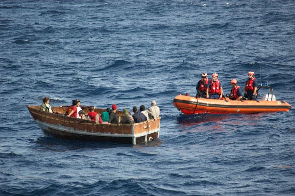 In this Dec. 30, 2014, photo provided by the U.S. Coast Guard, members of the U.S. Coast Guard Cutter Knight Island approach a boat with 12 Cuban migrants southwest of Key West, Fla. (AP Photo/U.S. Coast Guard)