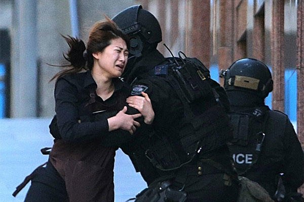 In this Dec. 15, 2014 file photo, a hostage runs to armed tactical response police officers for safety after she escaped from a cafe under siege at Martin Place in the central business district of Sydney, Australia. (AP Photo/Rob Griffith, File)