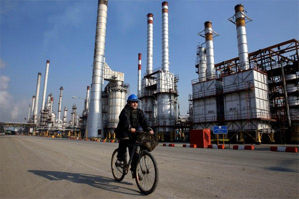 In this Monday, Dec. 22, 2014 photo, an Iranian oil worker rides his bicycle at the Tehran's oil refinery south of the capital Tehran, Iran. (AP Photo/Vahid Salemi)