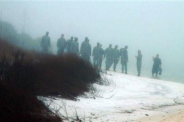 Military personnel wade in the water and search on the beach under heavy fog at Eglin Air Force Base, Fla., Wednesday, March 11, 2015, for the wreckage of a military helicopter that crashed with 11 service members aboard. (AP Photo/Melissa Nelson-Gabriel)