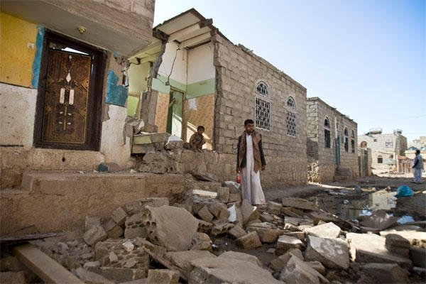 In this Tuesday, March 31, 2015 file photo, a Yemeni man stands near his house destroyed by Saudi airstrikes nearSanaa Airport, Yemen. Saudi Arabia and its allies plan an ambitious ground offensive on multiple fronts in Yemen. (AP Photo/Hani Mohammed)