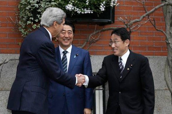 Secretary of State Kerry shakes hands with Japanese Foreign Minister Fumio Kishida, right, as Japanese Prime Minister Shinzo Abe, center, smiles in front of Kerry's residence Boston, Sunday, April 26, 2015.. (AP Photo/Steven Senne)