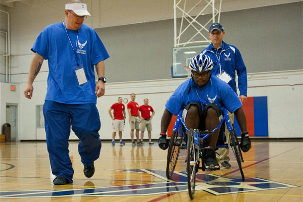 Air Force Tech. Sgt. Ryan Delaney, left, a wounded warrior mentor, watches Tremayne Maxwell, an Air Force wounded warrior athlete, perfect his wheelchair basketball skills at Eglin Air Force Base, April 13, 2015. U.S. Air Force photo/Samuel King Jr.