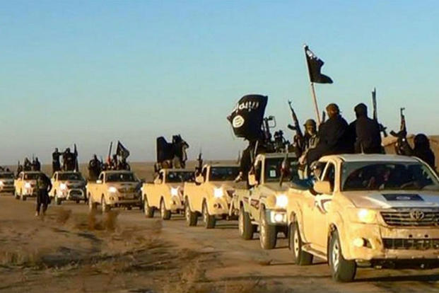 In this undated file photo released by a militant website, which has been verified and is consistent with other AP reporting, militants of the Islamic State group hold up their weapons and wave its flags in a convoy. (Militant website via AP, file)