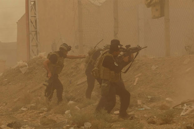 In this May 14, 2015 file photo, security forces defend their headquarters against attacks by Islamic State extremists during a sandstorm in the eastern part of Ramadi, the capital of Anbar province, Iraq. (AP Photo, File)