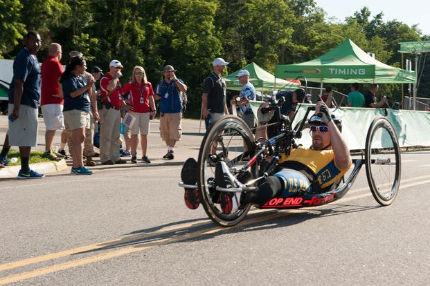 A participant in the Cycling competition of the 2015 Department of Defense (DoD) Warrior Games enters his final lap at Lejeune Hall Lot, Marine Corps Base Quantico, Va. (U.S. Marine Corps photo by Cpl. Diana Sims/Released)