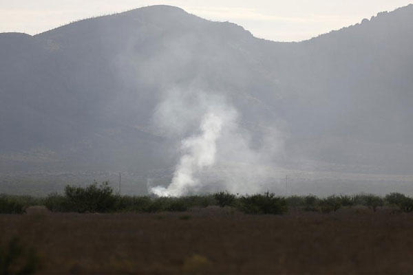 Smoke rises Thursday, June 25, 2015, from the site where an F-16 Fighting Falcon crashed Wednesday evening near Douglas, Ariz. (Mamta Popat/The Tucson Citizen via AP)