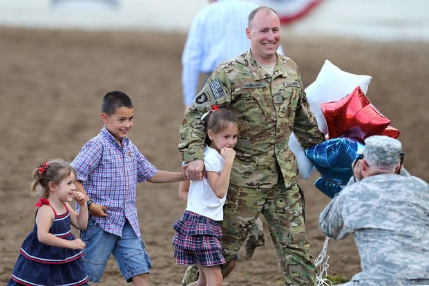 In this Friday, June 19, 2015 photo, Nevada Army National Guard Chief Warrant Officer Glen Spadin walks off the arena floor with his children after his surprise return from Afghanistan at the Reno Rodeo in Reno, Nev.  (AP Photo/Cathleen Allison)