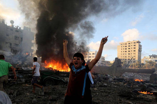 In this July 24, 2014 file photo, a Palestinian shouts in an area damaged in an Israeli airstrike in Gaza City, Gaza Strip. (AP Photo/Hatem Moussa, File)