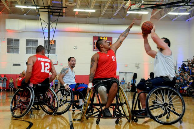 Marine Corps Cpl. Marcus Chischilly defends as retired Navy Chief Petty Officer Hector Varela takes a shot during the wheelchair basketball gold medal match at the 2015 DoD Warrior Games, June 23, 2015. (DoD photo by Shannon Collins)