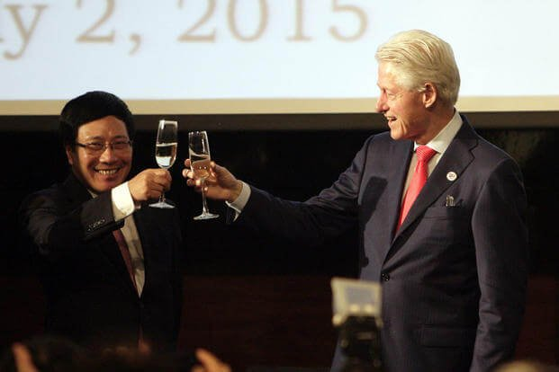 Former U.S. President Bill Clinton toasts with Vietnamese Foreign Minister Pham Binh Minh during an event celebrating the 20th anniversary of normalization of relations between the U.S. and Vietnam in Hanoi on July 2, 2015. (AP Photo/Tran Van Minh)