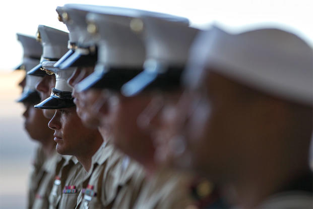U.S. Marines and sailors stand at attention during a ceremony honoring the remains of 36 unidentified Marines found at a World War II battlefield at Joint Base Pearl Harbor-Hickam, Sunday, July 26, 2015, in Honolulu. (AP Photo/Marco Garcia)