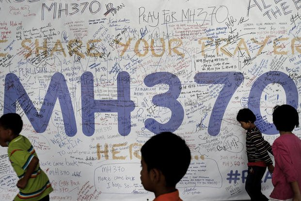 In this March 13, 2014, photo, children run past dedication messages left for passengers and others involved with the missing Malaysia Airlines jetliner MH370 on the walls of the Kuala Lumpur International Airport, in Malaysia. (AP Photo/Wong Maye-E)