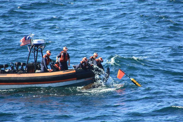 A small-boat crew deployed from the Coast Guard Cutter Campbell untangles a 6-foot long Leatherback turtle from fishing line 15 miles off Cape Elizabeth, Maine, Sept. 20, 2015. (U.S. Coast Guard photo)