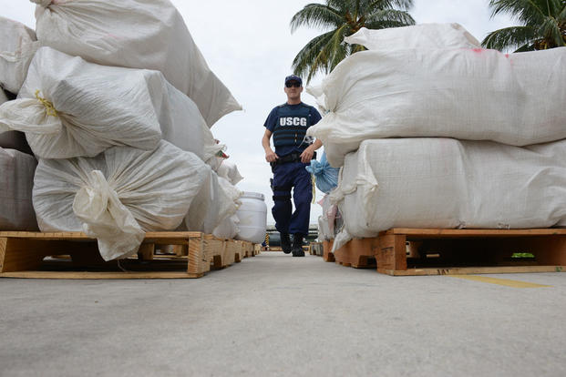 Lt. Michael Cortese directs the offload of seized cocaine and marijuana at Coast Guard Base Miami Beach, Fla., Sept. 29, 2015. (U.S. Coast Guard photo by Petty Officer 2nd Class Mark Barney)
