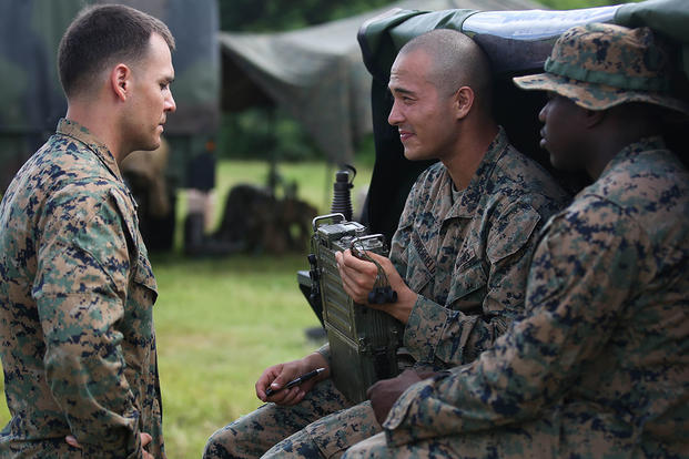 Cpl. Seth Dixon (left) speaks to Cpl. Terry Summerfield (center) and Cpl. John Boyd (right) at the Boondocker Training Area aboard Marine Corps Base Hawaii during training exercise Island Viper, Sept. 22, 2015. Photo By: Lance Cpl. Harley Thomas