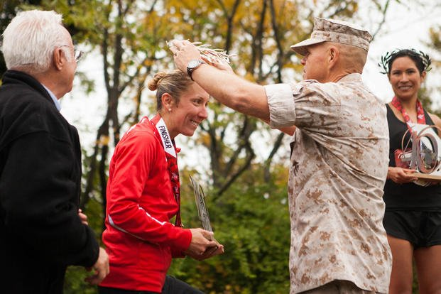 Marine Corps Capt. Christine Taranto, the silver female finisher of the 40th Marine Corps Marathon, accepts her wreath from Gen. Robert Neller, the 37th Commandant of the Marine Corps, in Arlington, Virginia, Oct. 25. (Photo By: Sgt. Justin M. Boling)