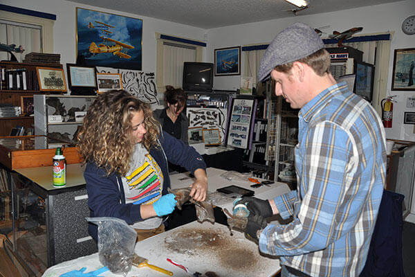 NHHC archaeologist Dr. George Schwarz, right, and graduate student Nicole Mauro clean artifacts recovered from the crash site of a World War II Navy aircraft as Maddeline Voas, center, photographs the artifacts. (U.S. Navy/Lt. Cmdr. Heidi Lenzini)