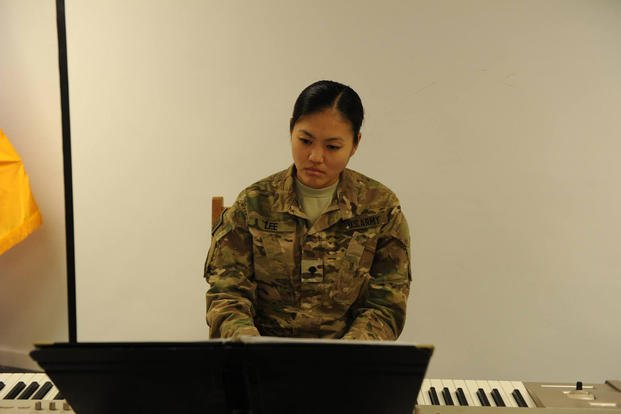 Army Spc. Anne Lee plays the piano during an event on Bagram Airfield in Afghanistan. (Photo: Kevin Walston)