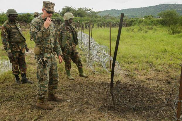 U.S. Marine Staff Sgt. Malachi McPherson and Uganda People's Defense Force soldiers observe the efficiency of their breach on a razor-wire obstacle during a breaching exercise at Camp Singo, Uganda, Dec. 1, 2015. (Photo: Cpl. Olivia McDonald)