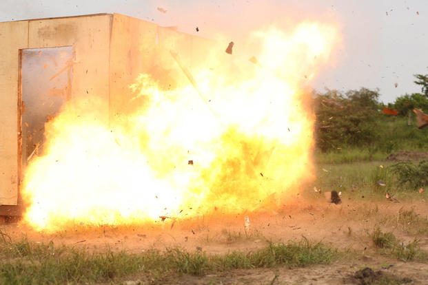 A Uganda's People Defense Force soldier detonates an oval charge on the wall of a notional objective position of desired entry while the team seeks cover around the corner of the position at Camp Singo, Uganda Nov. 25, 2015. (Photo: Cpl. Olivia McDonald)