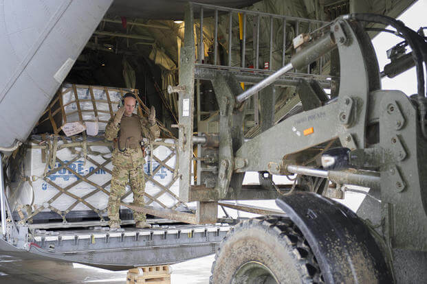 Staff Sgt. Justin King, a 774th Expeditionary Airlift Squadron loadmaster, guides a forklift toward the aft loading ramp of a C-130J Super Hercules at Camp Bastion, Afghanistan, Jan. 3, 2016. (U.S. Air Force photo/Tech. Sgt. Robert Cloys)