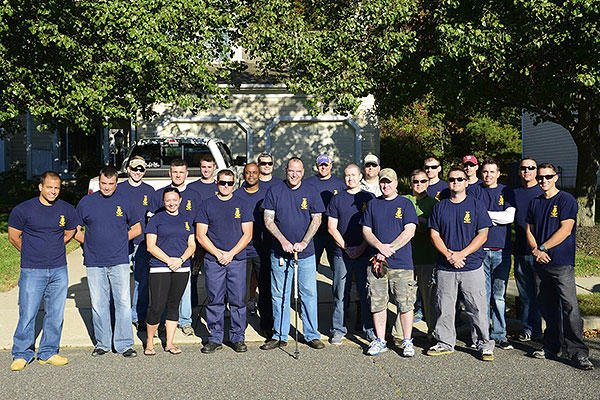 Coast Guard Chief Warrant Officer Richard Sambenedetto poses outside his home in New Jersey with 20 prospective chief petty officers who helped him out with landscaping and housework. (U.S. Coast Guard/Chief Petty Officer Nick Ameen)