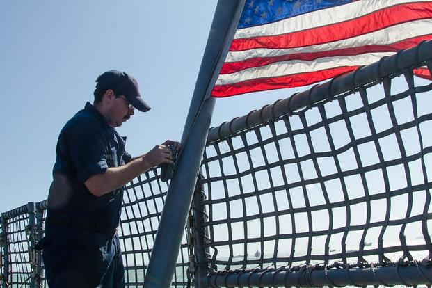 Aviation Machinist's Mate 1st Class Sean Wilde raises the colors aboard USS Fort Worth after the ship moored to the pier in Phuket, Thailand for a scheduled port visit. (Photo: Mass Communication Specialist 2nd Class Antonio Turretto Ramos)